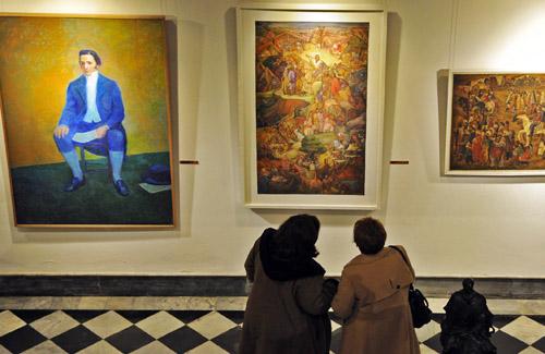 Visitantes de museos viendo cuadros
