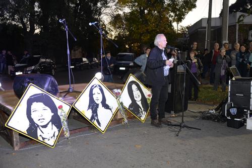 Maestro de ceremonias hablando junto al escenario con las placas de las tres jóvenes asesinadas.