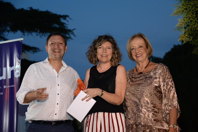 Mautone y Muñoz entregando la estatuilla a una de las autoras ganadoras