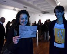 Una chica sostiene una fotografía perteneciente a la muestra.